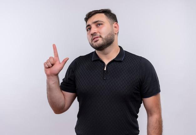 Giovane uomo barbuto in camicia nera che punta il dito cercando di ricordare