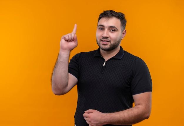 Giovane uomo barbuto in camicia nera che punta il dito indice in alto sorridente fiducioso avendo nuova idea