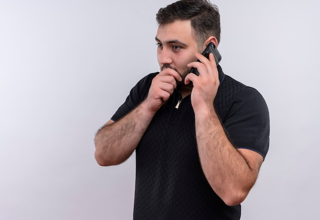 Young bearded man in black shirt   telling a secret while talking on mobile phone