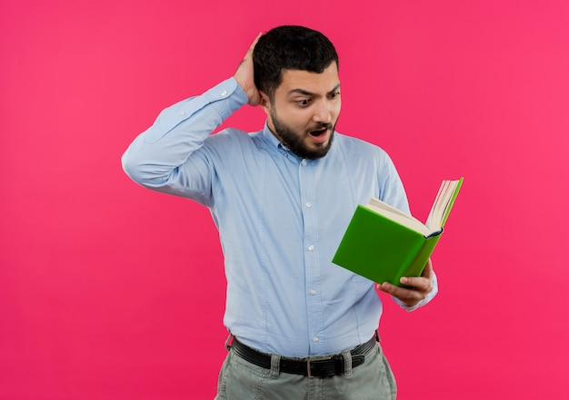 Young bearded man in blue shirt holding book looking at it being surprised and confused