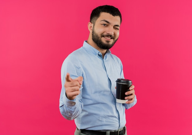 Young bearded man in blue shirt holding coffee cup pointign with index finger at camera smiling and winking