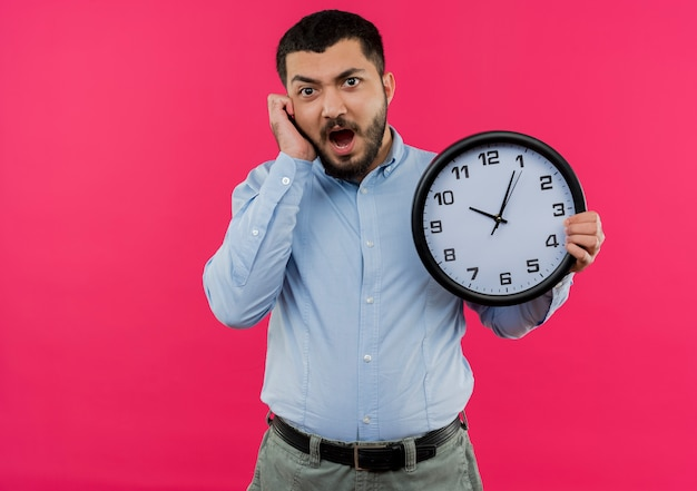Giovane uomo barbuto in camicia blu che tiene orologio da parete gridando in preda al panico