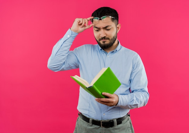 Young bearded man in blue shirt looking at book in his hands putting glasses off