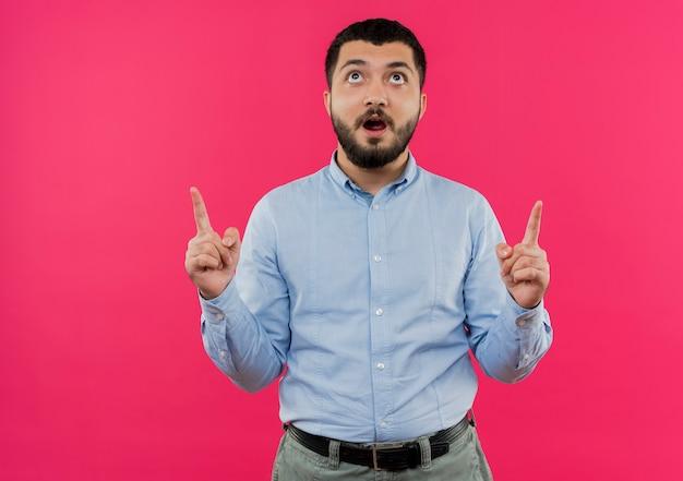 Giovane uomo barbuto in camicia blu che punta con il dito indice per essere sorpreso
