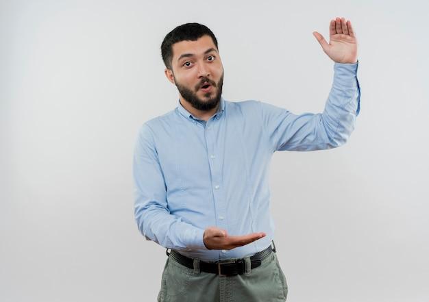Giovane uomo barbuto in camicia blu che mostra gesto di grandi dimensioni con le mani di essere sorpreso