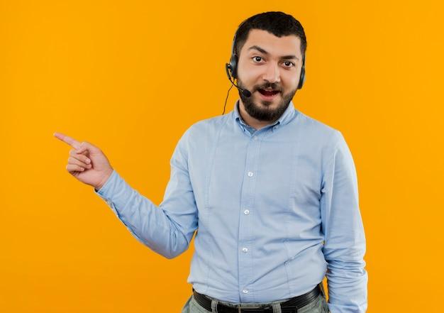 Giovane uomo barbuto in camicia blu con cuffie con microfono pointign con il dito indice a lato sorridente