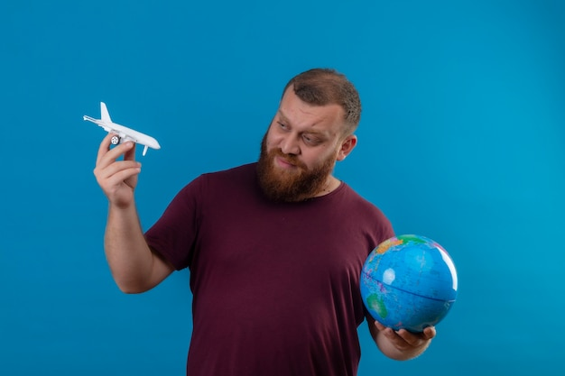 Young bearded man in brown t-shirt holding globe and toy airplane looking at toy with skeptic expression on face