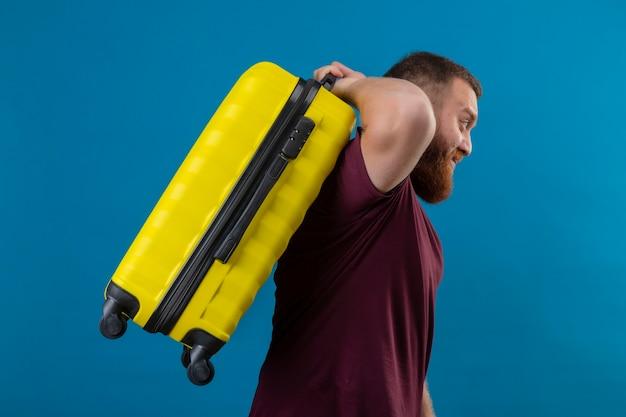 Giovane uomo barbuto in maglietta marrone che tiene la valigia di viaggio che sembra stanco e annoiato lateralmente
