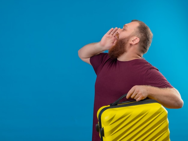 Young bearded man in brown t-shirt holding travel suitcase shouting or calling someone with hand near mouth
