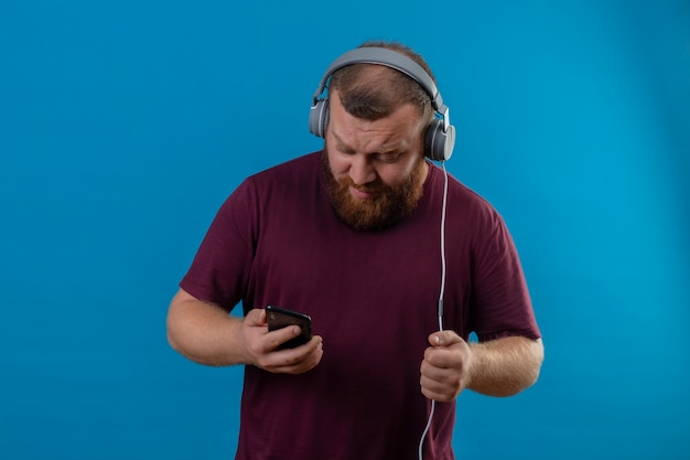Young bearded man in brown t-shirt with headphones holding mobile phone searching favorite song