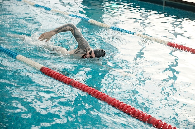 Young bearded man in cap and goggles swimming stroke in modern pool
