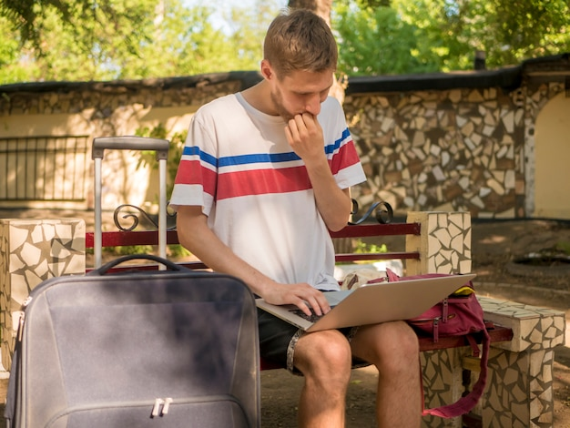 Young bearded man in casual sitting on bench with large cases of luggage and working on laptop