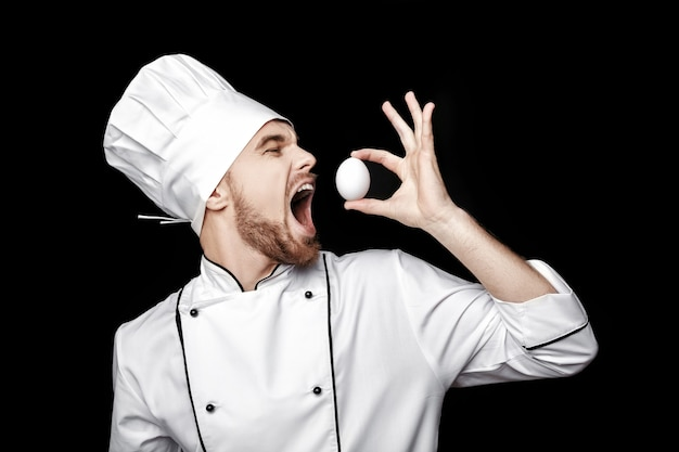 白い制服を着た若いひげを生やした男のシェフは、黒い背景に卵を保持します。