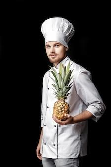 白い制服を着た若いひげを生やした男のシェフは、黒の背景に新鮮なパイナップルを保持します。