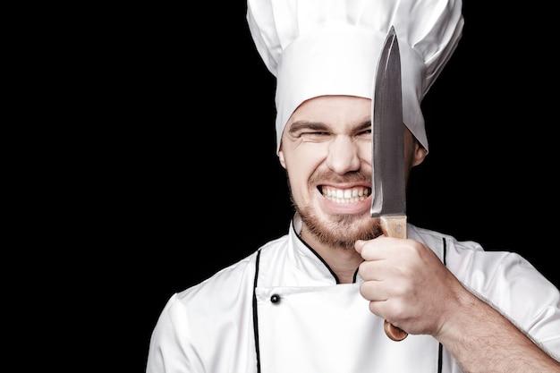 白い制服を着た若いひげを生やした男のシェフは、黒い背景の上の顔の前にナイフを保持します。
