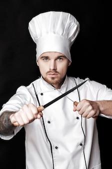 白い制服を着た若いひげを生やした男のシェフは、黒の背景に2つのナイフを保持します。