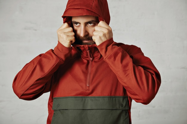 Young bearded man covering his face with the hood of his brick red and dark grey anorak on white