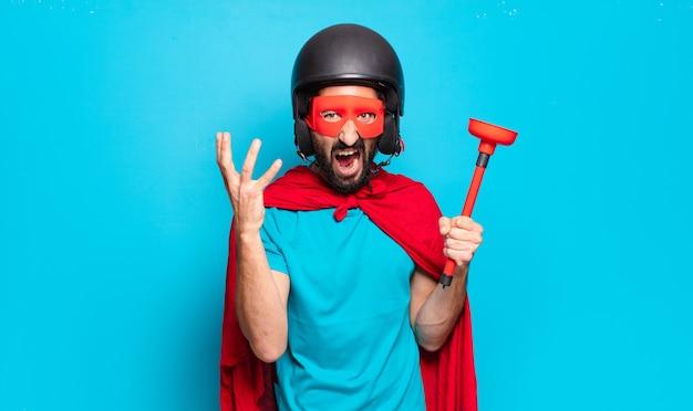 젊은 수염 남자. 헬멧과 마스크가있는 미친 유머러스 한 슈퍼 영웅
