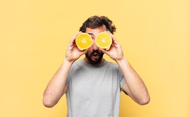 Молодой бородатый мужчина сидит на диете с удивленным выражением лица и держит апельсин