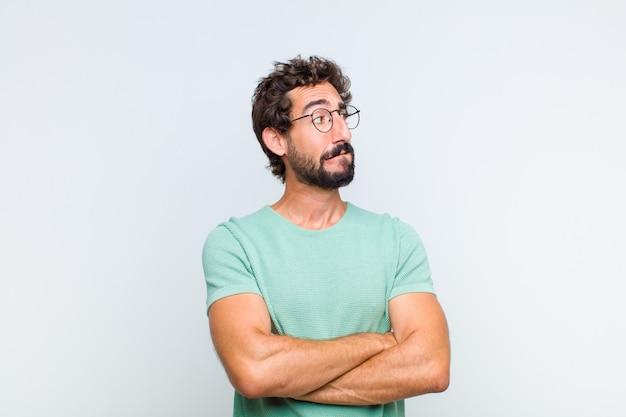 Молодой бородатый мужчина сомневается или думает
