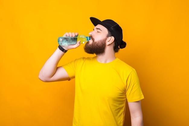 黄色の水を飲む若いひげを生やした男