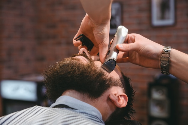 Молодой бородатый мужчина во время стрижки бороды с помощью триммера в парикмахерской