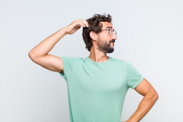 無知で混乱している若いひげを生やした男、解決策を考えて、腰に手を、頭に他の人、背面図