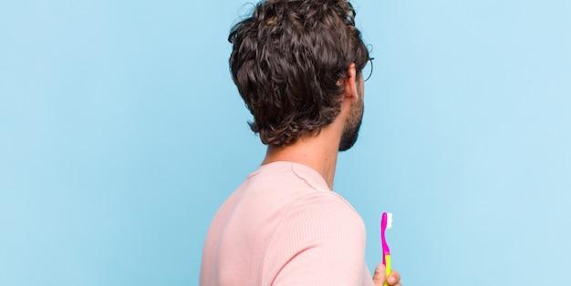 若いひげを生やした男は、混乱したり、満腹になったり、疑問や質問を感じたり、疑問に思ったり、腰に手を当てたり、背面図を表示したりします