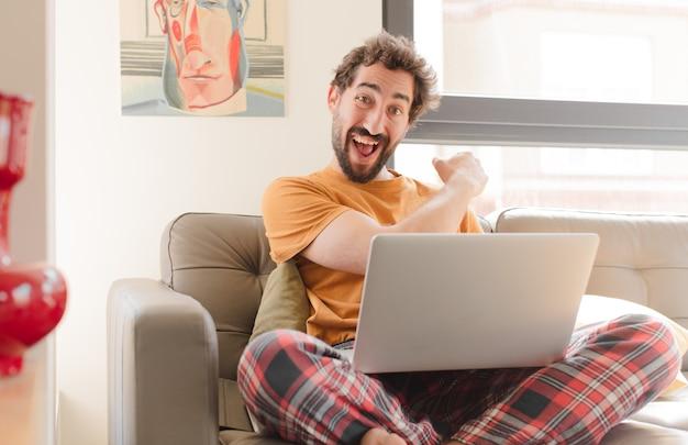 Молодой бородатый мужчина чувствует себя счастливым, позитивным и мотивированным к успеху, когда сталкивается с проблемой или празднует хорошие результаты и сидит с ноутбуком