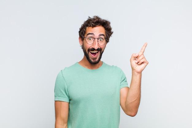 アイデアを実現した後、幸せで興奮した天才のように感じる若いひげを生やした男、元気に指を上げる、エウレカ!