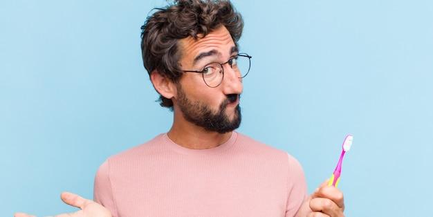 Молодой бородатый мужчина смущен и сбит с толку, неуверенный в правильном ответе или решении, пытается сделать выбор