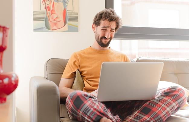 Молодой бородатый мужчина грустит и плаксирует с несчастным взглядом, плачет с негативным и разочарованным отношением и сидит с ноутбуком