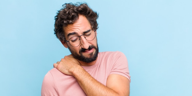 Молодой бородатый мужчина чувствует усталость, стресс, тревогу, разочарование и депрессию, страдает от боли в спине или шее