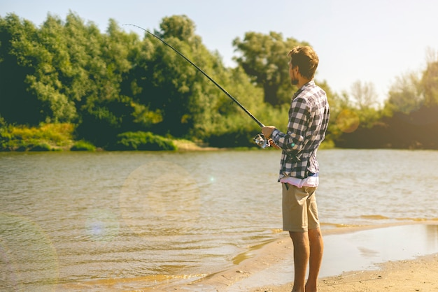 Young bearded man fishing standing on the sandy river bank with fish-rod during summer.