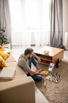 젊은 수염 난된 남자는 집에서 태블릿에 통신 앱을 사용하여 친구와 놀고 체스 게임에 집중