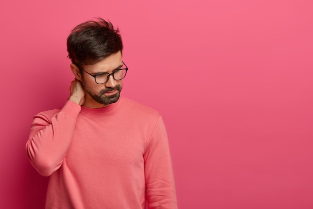 젊은 수염 난 남자가 아래로 집중하고, 목에 통증이 있고, 마사지를 받고, 손으로 만집니다.