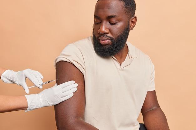若いひげを生やした男は、ベージュの壁に対するコロナウイルスのポーズを停止するために腕に注射を取得します