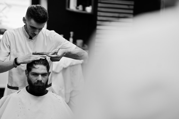 Young bearded man getting haircut by hairdresser while sitting in chair at barbershop. barber soul.