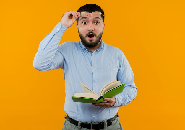 Young bearded man in glasses and blue shirt holding book being amazed putting his glasses off