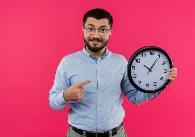 Young bearded man in glasses and blue shirt holding wall clock pointing with index finger at it smiling with happy face