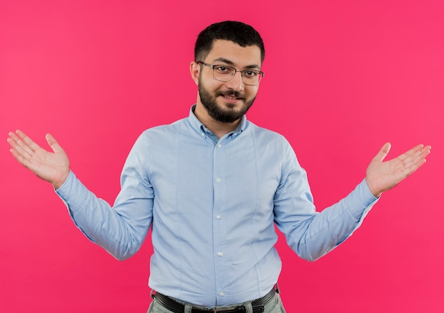Young bearded man in glasses and blue shirt spreading arms to the sides smiling with happy face