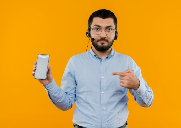 Young bearded man in glasses and blue shirt with headphones with microphone showing smartphone pointing with index finger at it with serious face