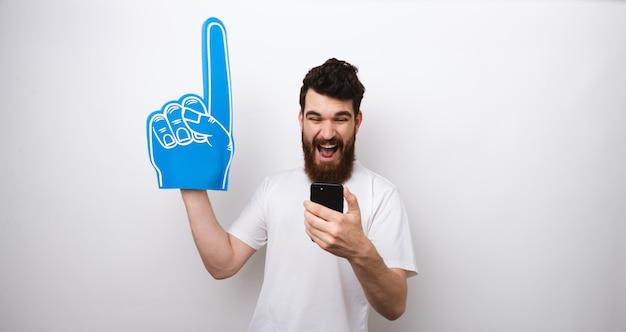 若いあごひげを生やした青い泡指を押しながら彼の携帯電話を見ています。