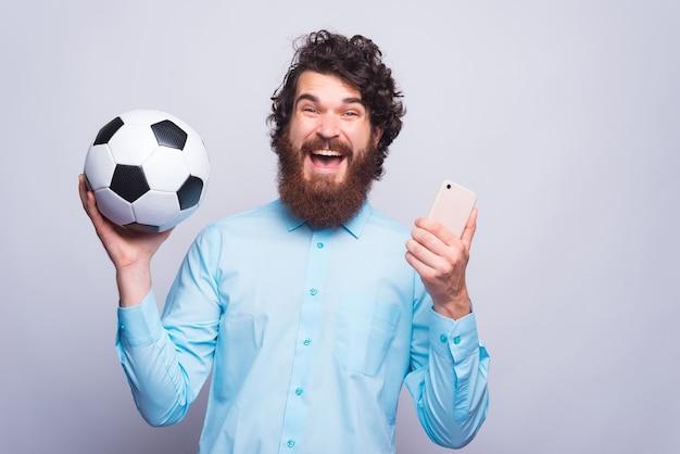 Молодой бородатый мужчина держит мобильный телефон и футбольный мяч