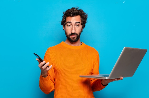 Молодой бородатый мужчина держит ноутбук. концепция социальных сетей