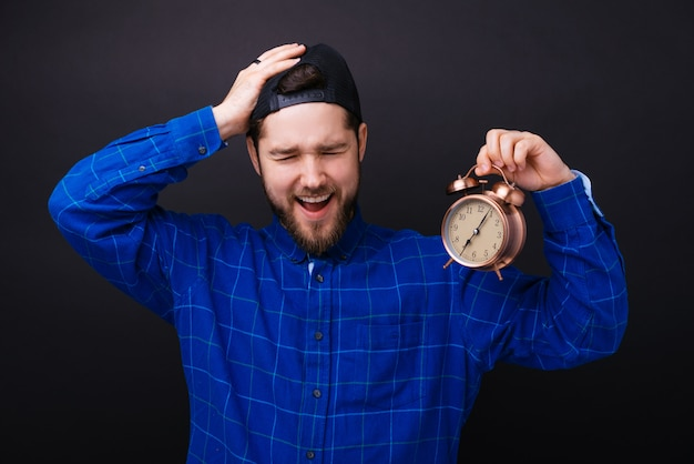 Young bearded man holding an alarm clock and being late making a forget gesture.