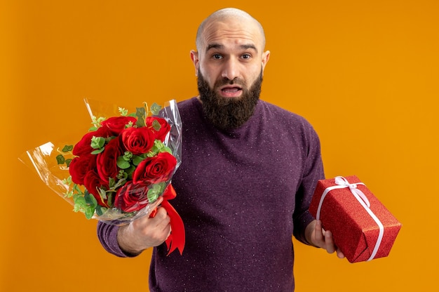 Young bearded man holding bouquet of red roses and a present looking at camera surprised valentines day concept standing over orange background