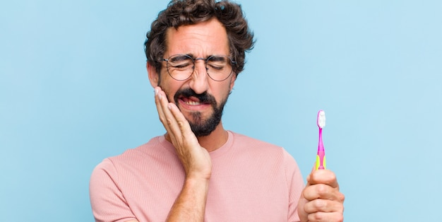 頬を抱え、痛みを伴う歯痛に苦しんでいる、気分が悪く、惨めで不幸な、歯科医を探している若いひげを生やした男
