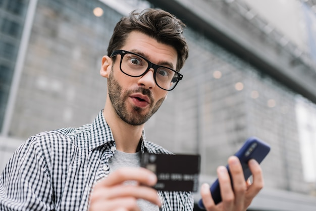 Young bearded man holding credit card and smartphone, making payment. hipster with emotional face shopping online. online banking concept