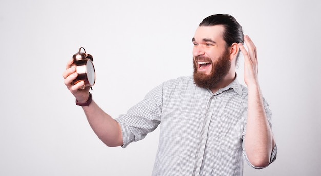Young bearded man holding a little clock is looking at it amazed near a white wall